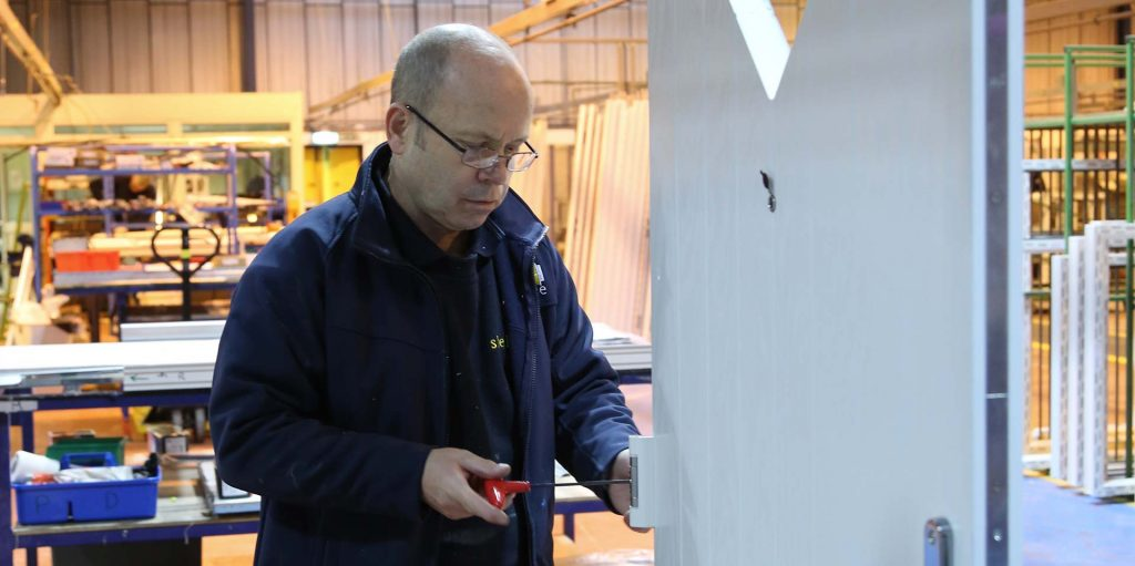 A skilled engineer working on finishing a composite door ready for installation
