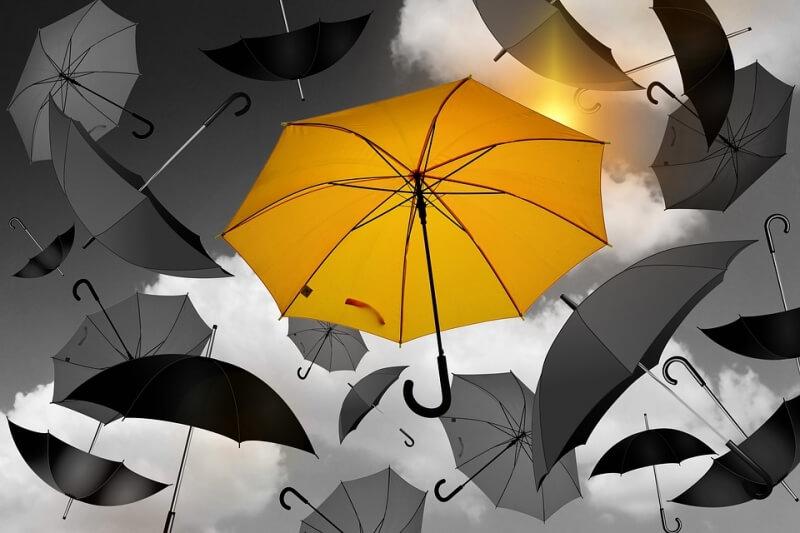 Yellow umbrella around grey umbrellas
